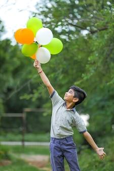 Śliczny mały indyjski chłopiec z trójkolorowymi balonami i świętuje dzień niepodległości lub republiki indii