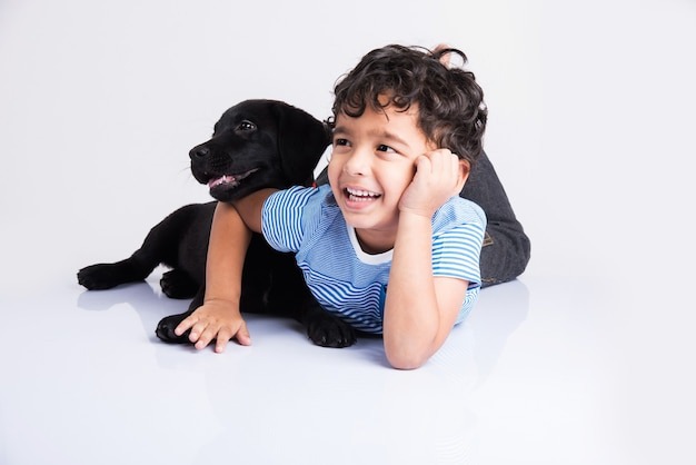 Śliczny mały indyjski lub azjatycki chłopiec bawi się ze szczeniakiem black labrador retriever leżąc lub siedząc na białym tle