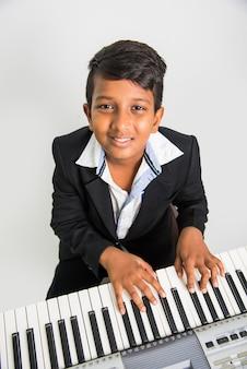 Śliczny mały indyjski lub azjatycki chłopiec grający na pianinie lub klawiaturze, instrumencie muzycznym, na białym tle