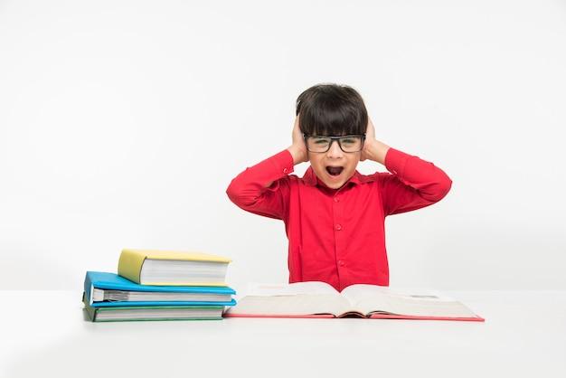 Śliczny mały indyjski lub azjatycki chłopiec trzymający lub czytający książkę nad stołem do nauki lub nad białą podłogą, odizolowany na białym tle