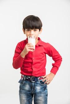 Śliczny mały indyjski lub azjatycki zabawny chłopiec trzymający lub pijący szklankę mleka, odizolowany na białym tle