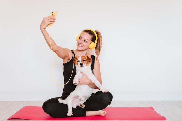 Śliczny mały jack russell pies robi joga na macie w domu z jej właścicielem. młoda kobieta, słuchanie muzyki na żółty telefon komórkowy i słuchawki. zdrowy styl życia w pomieszczeniu