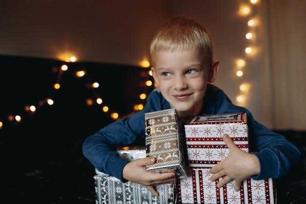 Śliczny mały kaukaski chłopiec ubrany w piżamę leżący na łóżku otoczony świątecznymi prezentami czekającymi