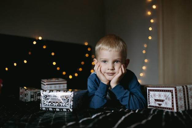 Śliczny mały kaukaski chłopiec ubrany w piżamę leżący na łóżku otoczony świątecznymi prezentami