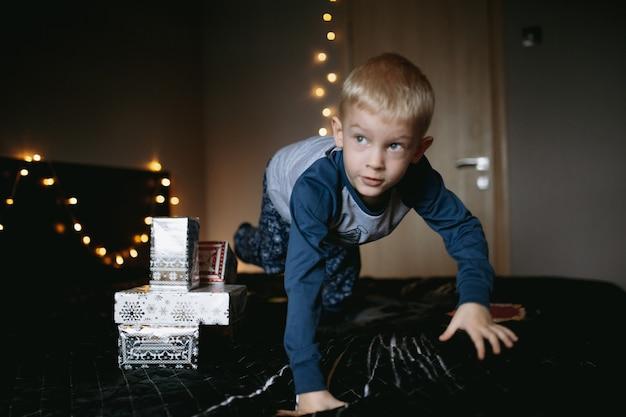 Śliczny mały kaukaski chłopiec ubrany w piżamę skaczący na łóżku otoczony świątecznymi prezentami