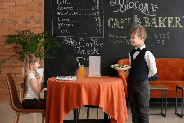 Śliczny mały kelner obsługujący klienta w restauracji?