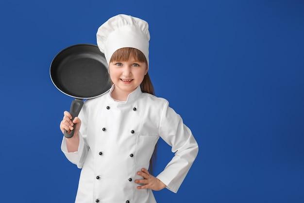 Śliczny mały kucharz na kolorowej powierzchni