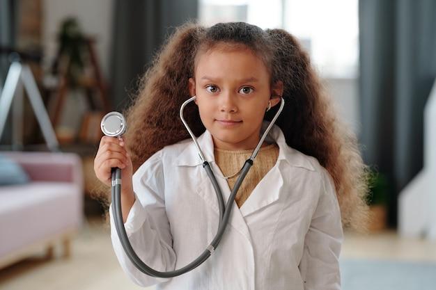 Śliczny mały lekarz trzymający stetoskop i patrzący na ciebie