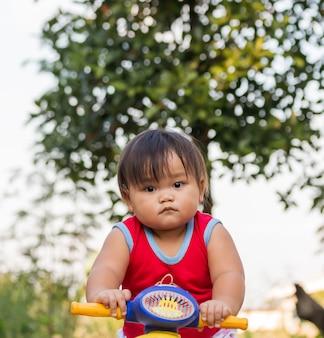 Śliczny mały rowerzysta na drodze z motocyklem. młoda dziewczyna na zabawkarskim motocyklu. mała dziewczynka uczy się jeździć pierwszy rower w naturze