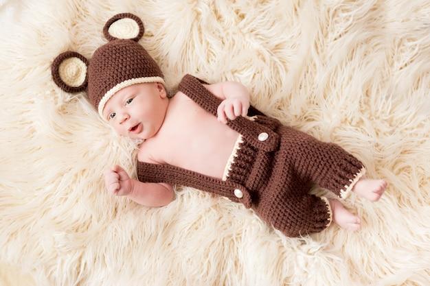 Śliczny mały szczęśliwy dziecko kłama w niedźwiadkowym kostiumu na bielu. noworodka w kapeluszu z uszami na białym