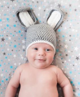 Śliczny mały szczęśliwy dziecko kłama w zając kostiumu na bielu. noworodka w kapeluszu z uszami na białym