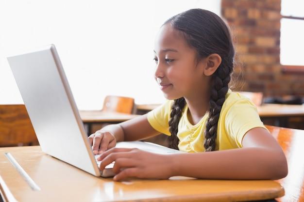 Śliczny mały uczeń patrzeje laptop w sala lekcyjnej
