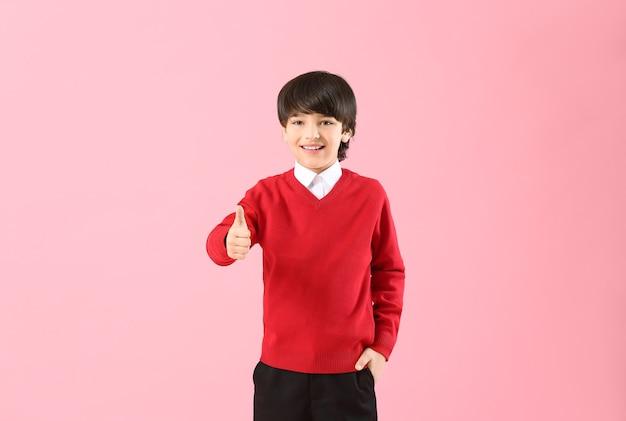 Śliczny mały uczeń pokazujący kciuk w górę na kolorowym tle