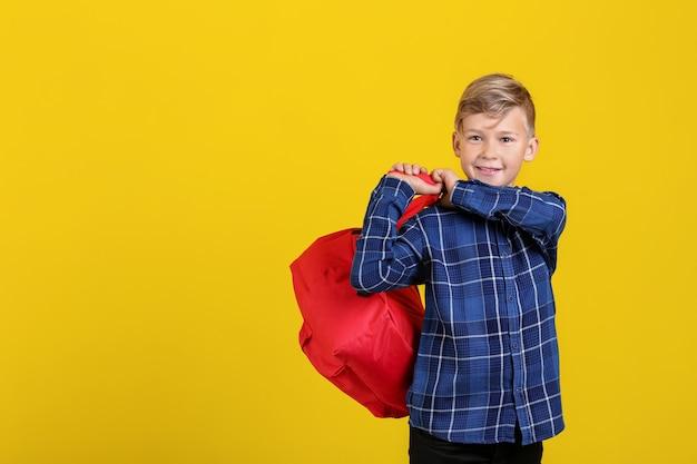 Śliczny mały uczeń z plecakiem na kolorowej powierzchni