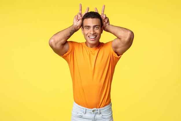 Śliczny męski i głupiutki latynoski chłopak w pomarańczowej koszulce, wykonaj gest pokoju, uszy królika za głową, uśmiechając się radośnie, naśladuj królika, aby wygłupiać się z siostrzenicą na żółtym tle