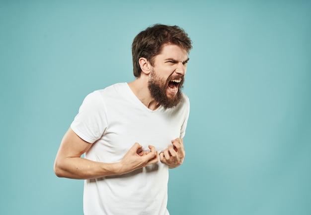 Śliczny mężczyzna na niebieskim tle gesty rękami podkreśla krzyk oburzenie drażliwości