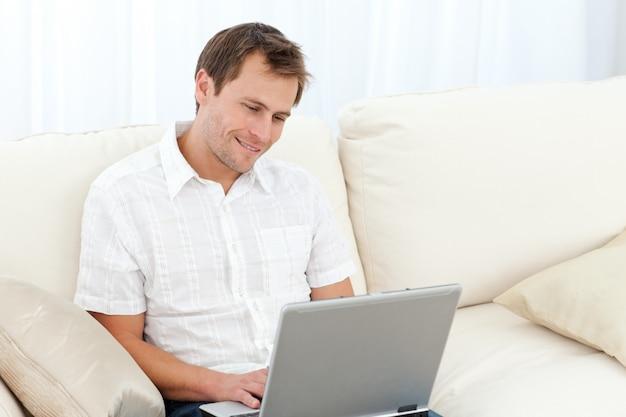 Śliczny mężczyzna surfing na sieci na kanapie
