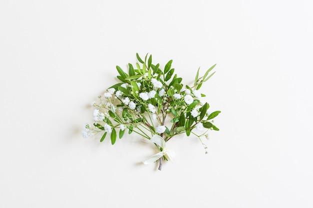 Śliczny miniaturowy wiosenny bukiet gałązek z zielonymi liśćmi i małymi kwiatami łyszczec. jasne pastelowe tło. pojęcie dnia kobiet, walentynki, urodziny, wakacje. cope, widok z góry, leżał płasko.