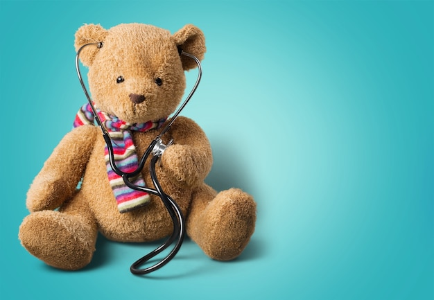 Śliczny miś, na białym tle, trzymając stetoskop.