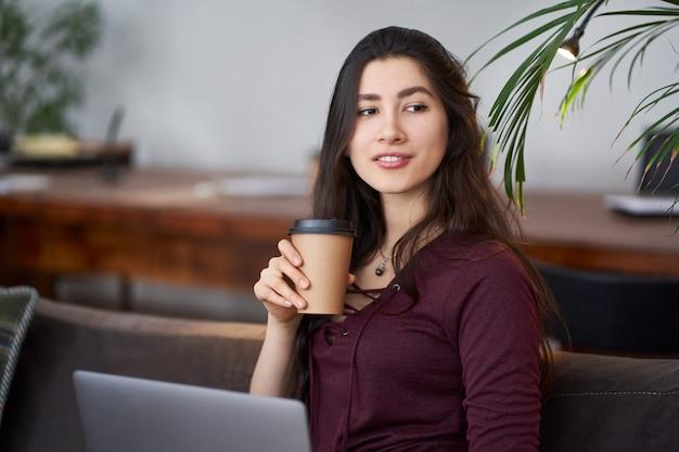 Śliczny młodej dziewczyny obsiadanie na leżance z kawą i laptopem