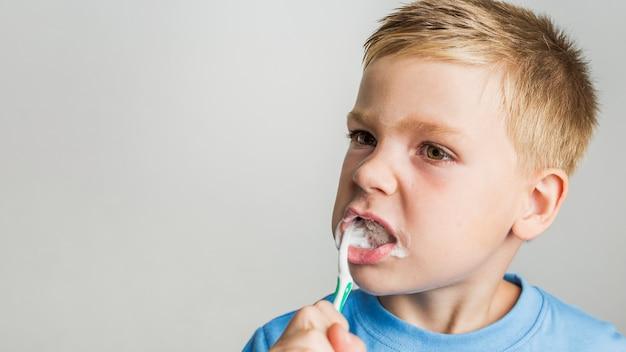 Śliczny młody chłopiec szczotkować zęby