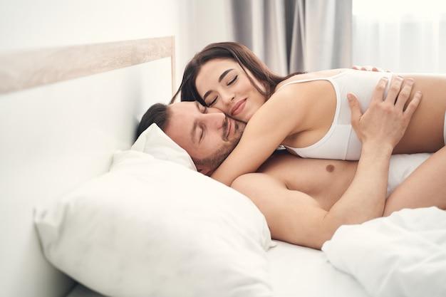 Śliczny młody mężczyzna rasy kaukaskiej i jego zadowolona żona leżąc w łóżku z zamkniętymi oczami