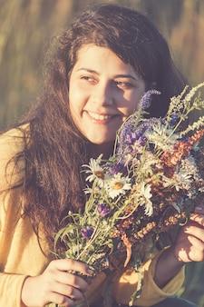 Śliczny młody uśmiechnięty dziewczyna portret z polem kwitnie podczas lato zmierzchu