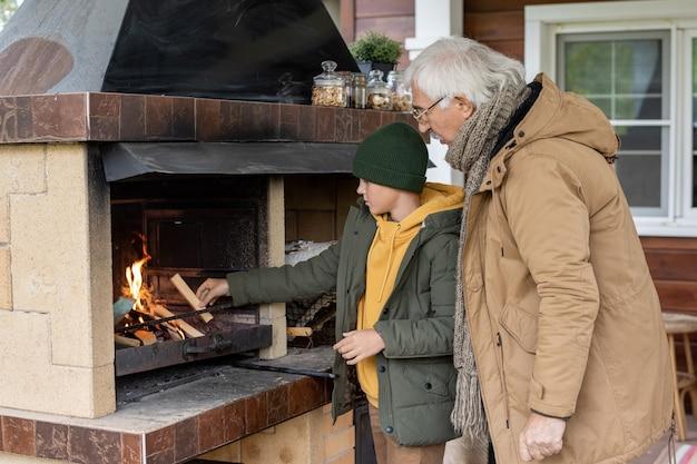 Śliczny młodzieniec lub nastolatek w ciepłej kurtce i czapce, stojący przy kominku, podczas rozpalania drewna na opał ze swoim dziadkiem w pobliżu