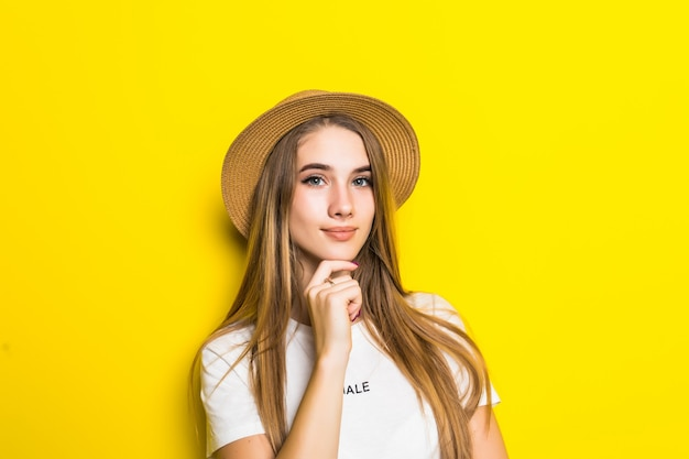 Śliczny model w białej koszulce i kapeluszu wśród pomarańczowego tła z śmieszną buzią