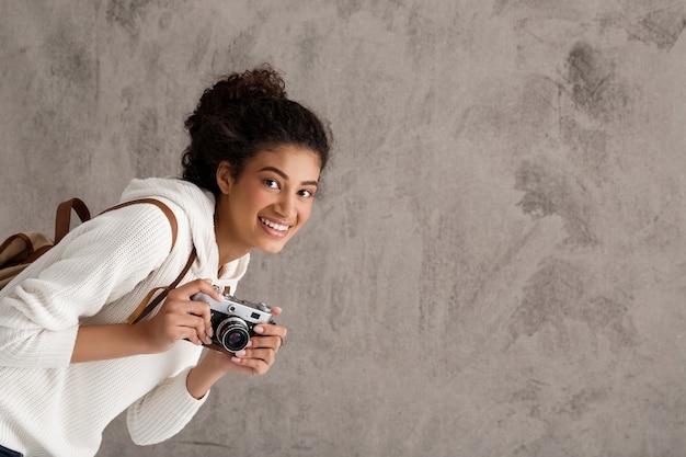 Śliczny modniś kobiety fotograf, szuka ładnego strzał