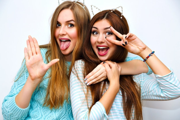 Śliczny modowy portret ślicznych sióstr, które razem się bawią, przytulają i szaleją, zabawne kocie uszy, miętowe zimowe swetry, biała ściana, najlepsi przyjaciele, radość, trend, relacje, szczęśliwy, naturalny makijaż.