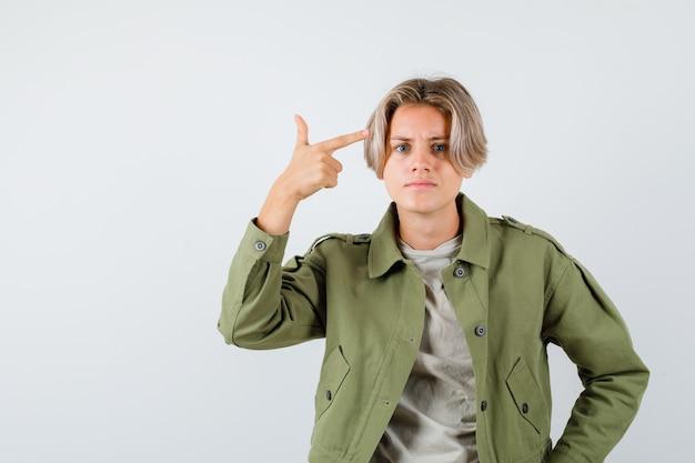 Śliczny nastolatek wskazujący na głowę w zielonej kurtce i patrzący na zakłopotanie