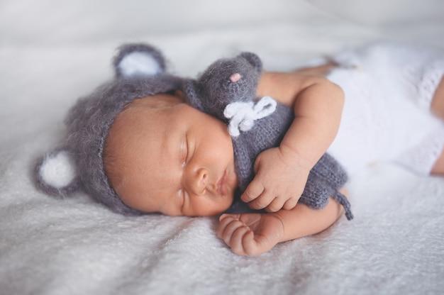 Śliczny noworodek chłopczyk z zabawką śpi w łóżeczku w dzianinowym garniturze z uszami.