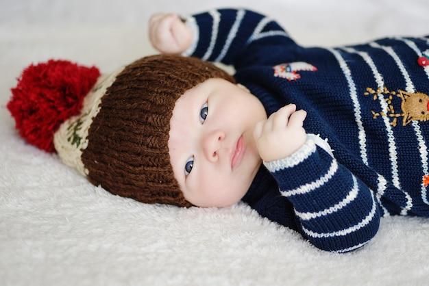 Śliczny noworodek w ciepłej wełnianej czapce i swetrze