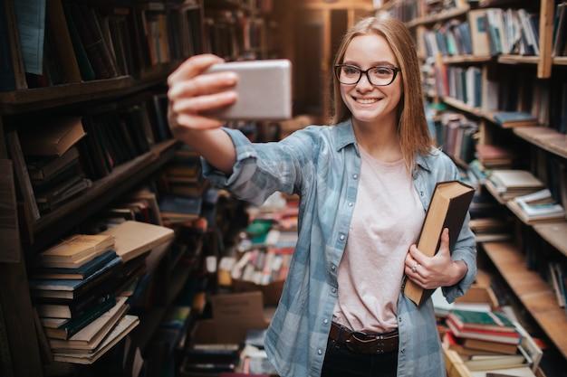 Śliczny obrazek blondynki dziewczyna bierze selfie. patrzy na telefon i uśmiecha się. te dziewczyny są w dużej bibliotece publicznej.
