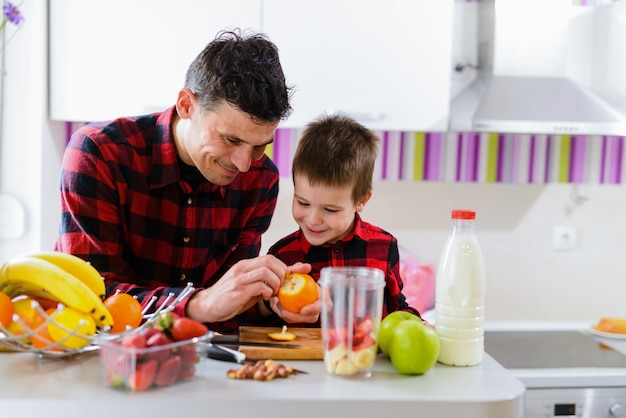 Śliczny ojciec i syn robi zdrowemu śniadaniu wpólnie. siedząc przy kuchennym stole pełnym świeżych owoców.