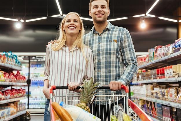 Śliczny para sklep spożywczy robi zakupy wpólnie