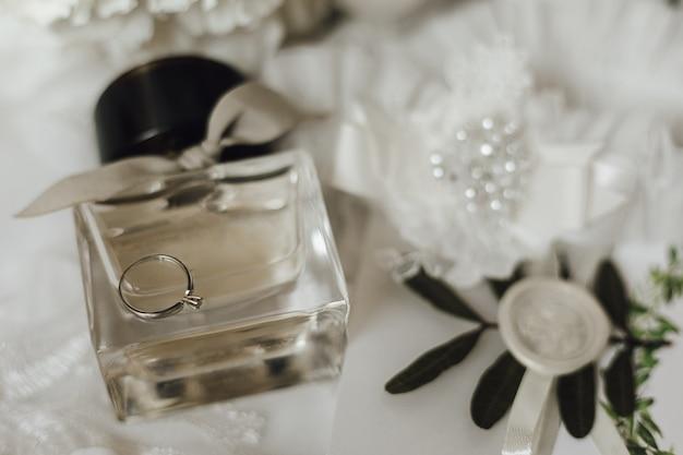 Śliczny pierścionek zaręczynowy wykonany z białego złota z brylantem na szklanej butelce z perfumami