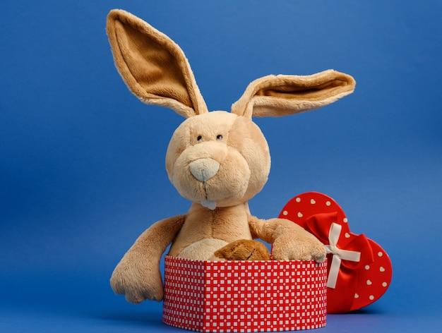 Śliczny pluszowy królik trzymający pudełko przewiązane czerwoną jedwabną wstążką, niebieskie tło, z bliska