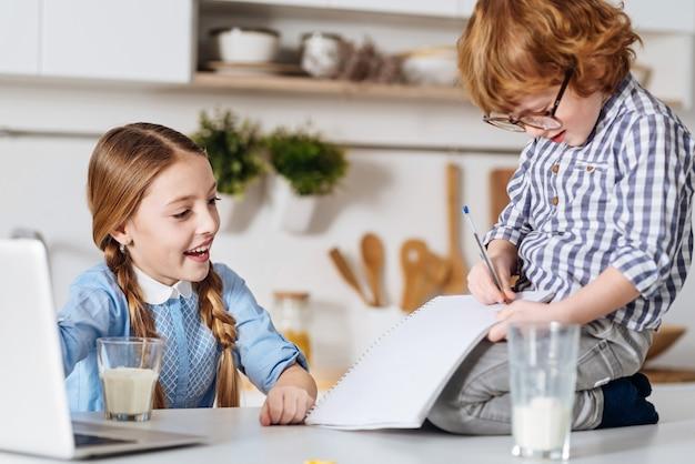 Śliczny pomocnik. produktywna pracowita inteligentna dziewczyna pomaga swojemu rodzeństwu w opracowaniu eseju, jednocześnie dyktując kilka kluczowych punktów, a jej brat je odnotowuje