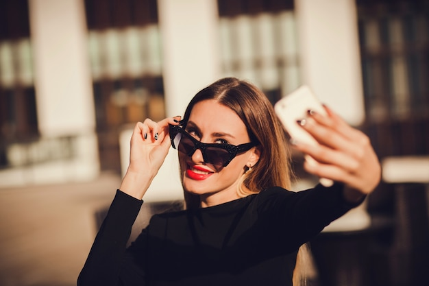 Śliczny portret młoda atrakcyjna kobieta trzyma smartphone i bierze selfie portret.