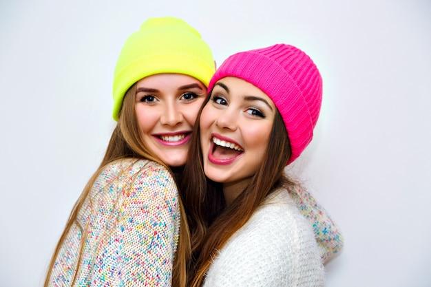 Śliczny pozytywny portret najlepszej przyjaciółki, ładne młode kobiety, czas zimowy, neonowe czapki, przytulne swetry, uściski i dobra zabawa, naturalny świecący makijaż, uśmiech dwóch sióstr, radość, para, emocje, biała ściana.