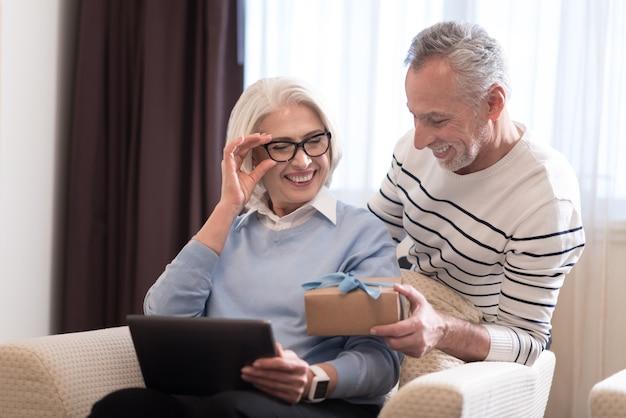 Śliczny prezent. zachwycony, uśmiechnięty starszy mężczyzna trzymający prezent, stojąc obok sofy i przytulając żonę