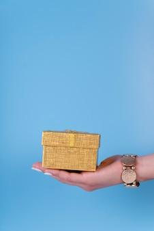 Śliczny prezenta pudełko trzymający w ręce na kopii przestrzeni tle