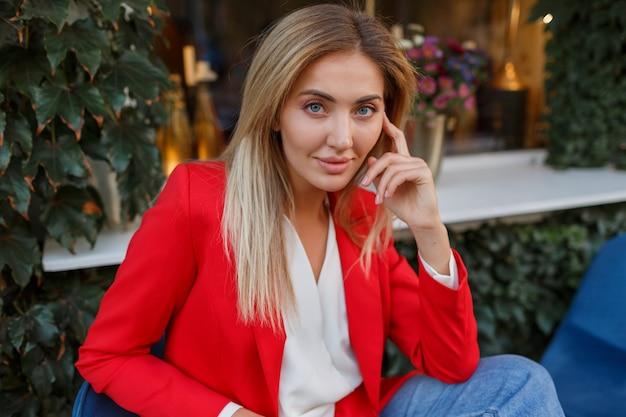Śliczny przystojny blond kobieta w czerwonej kurtce pozuje w miejskiej kawiarni