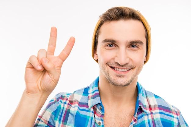 Śliczny przystojny młody człowiek gestykuluje dwa palce