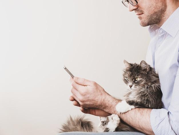 Śliczny, puszysty kotek i mężczyzna z telefonem. koncepcja opieki nad zwierzętami