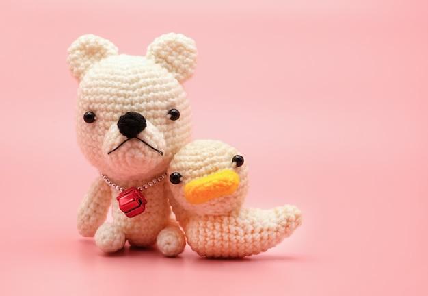 Śliczny ręcznie robiony dzianinowy miś i kaczka na białym tle na pastelowym różowym tle z miejscem na kopię