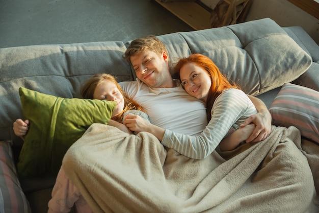 Śliczny. rodzina spędza miło czas razem w domu, wygląda na wesołą i pogodną. mama, tata i córka bawią się, leżąc na kanapie. razem, domowy komfort, miłość, koncepcja relacji.