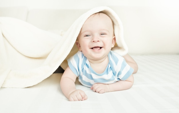 Śliczny roześmiany 6-miesięczny chłopiec leżący pod kocem na łóżku